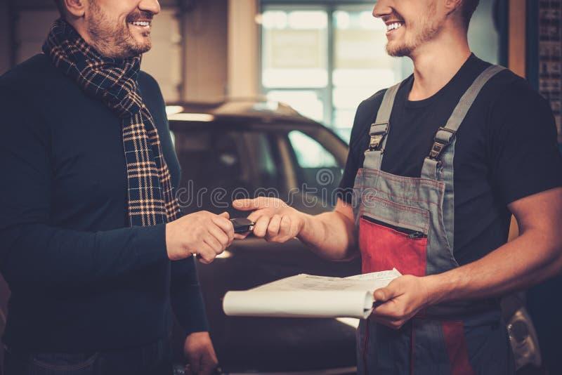 Bilmekaniker som ger klienttangenter till hans reparerade bil i service för auto reparation royaltyfri bild