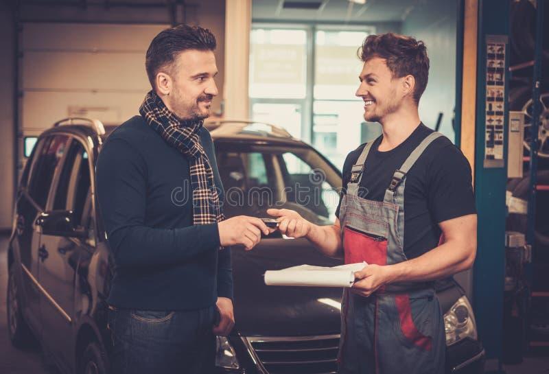 Bilmekaniker som ger klienttangenter till hans reparerade bil i service för auto reparation royaltyfria foton