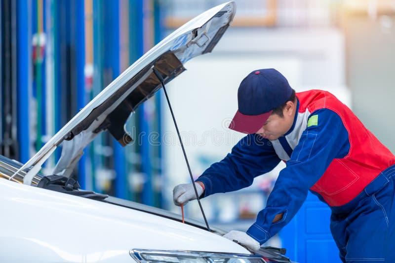 Bilmekanikern för den unga mannen i en mitt för bilreparationsservice analyserar motorproblem och kontrollerar motorn Arbete f?r  royaltyfria foton