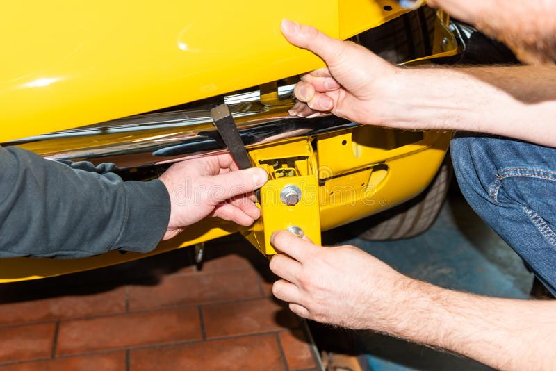 Bilmekanikern skruvar bildelar tillsammans igen efter återställande - Serie reparationsseminarium royaltyfria foton