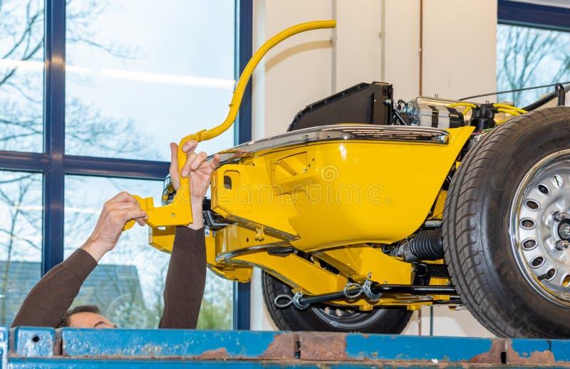 Bilmekanikern skruvar bildelar tillsammans igen efter återställande - Serie reparationsseminarium arkivbild
