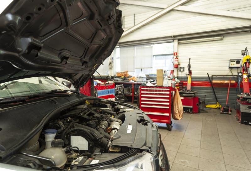 Bilmotor under reparation i garaget med modern utrustning Ov arkivbilder