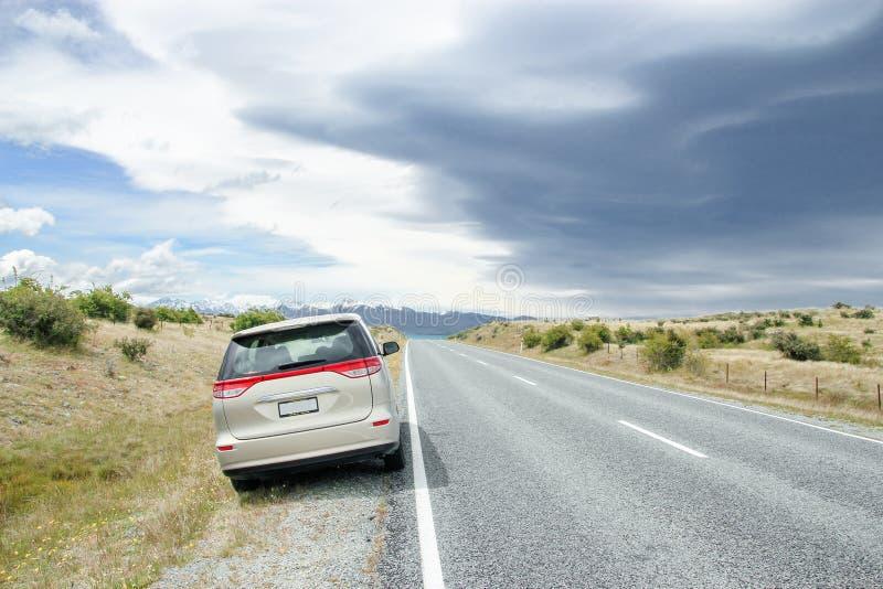 Bilparkering på sidan av vägen som leder för att snöa berg royaltyfria bilder