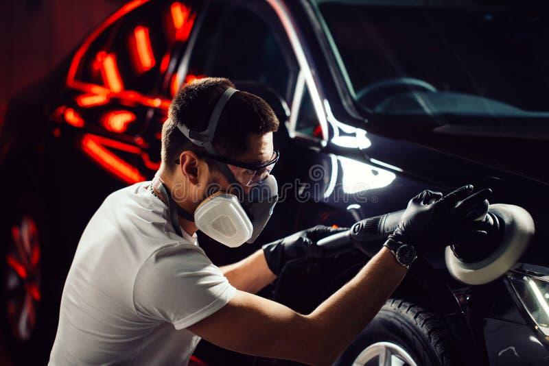 Bilpolermedelvax arbetaren räcker att rymma en polisher arkivfoton
