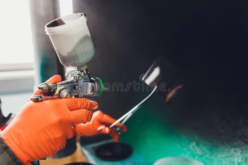Bilreparationsservice Arbetarmålare som kontrollerar färg som matchar, innan att måla bespruta svart flytande på den passande pla fotografering för bildbyråer