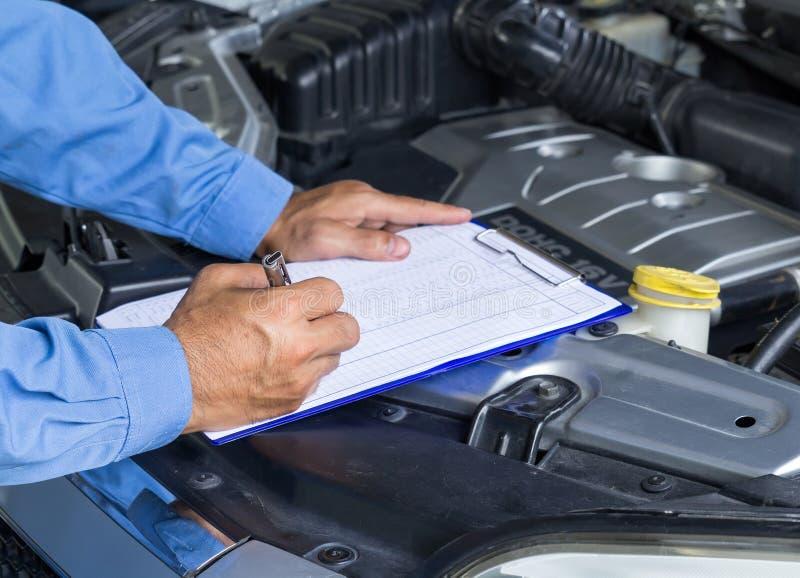 Bilreparationsservice, auto mekaniker som kontrollerar bilmotorn royaltyfri bild