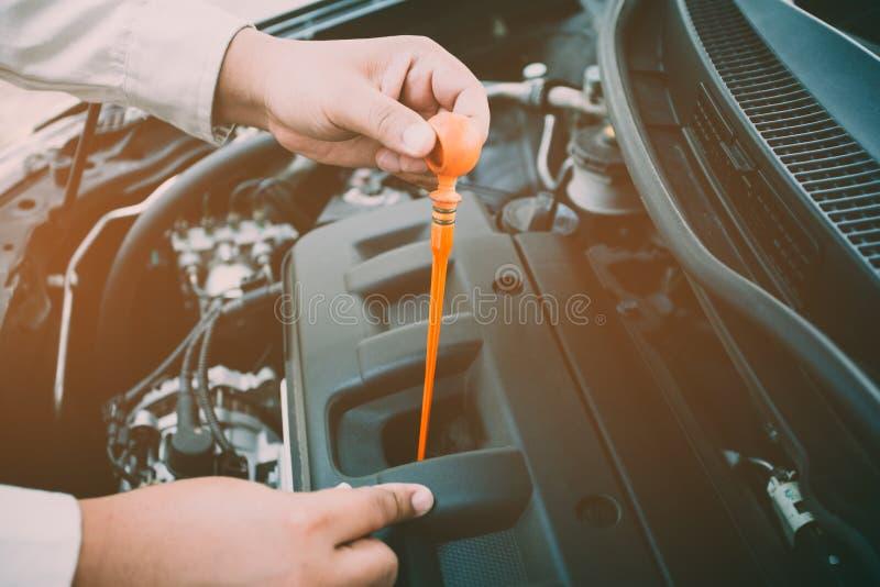 Bilreparationsservice, auto mekaniker som kontrollerar den olje- nivån i en motor royaltyfri foto