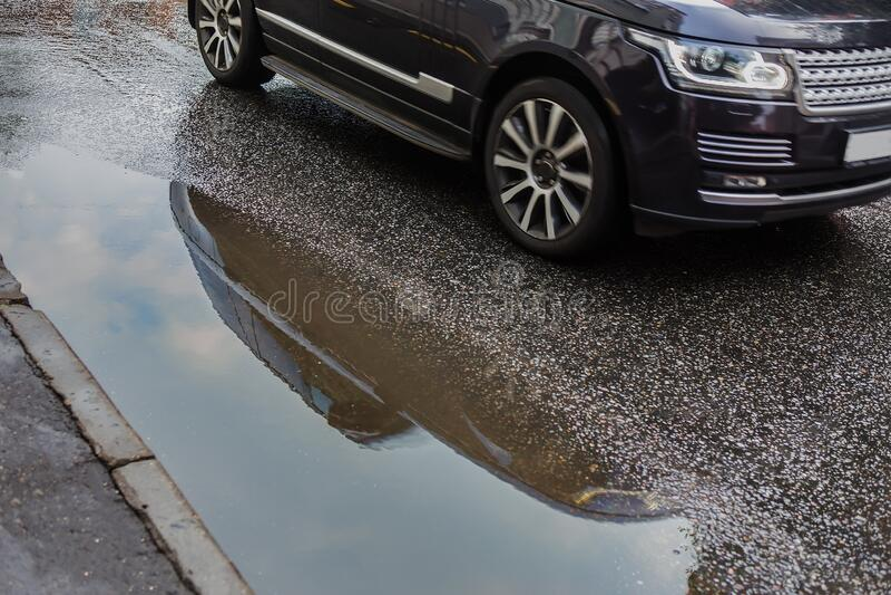 bilrider förbi en puddle på vägen royaltyfri bild