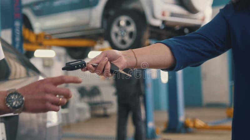 Bilseminarium - kvinnan ger tangenterna av bilen för mekaniker royaltyfri fotografi