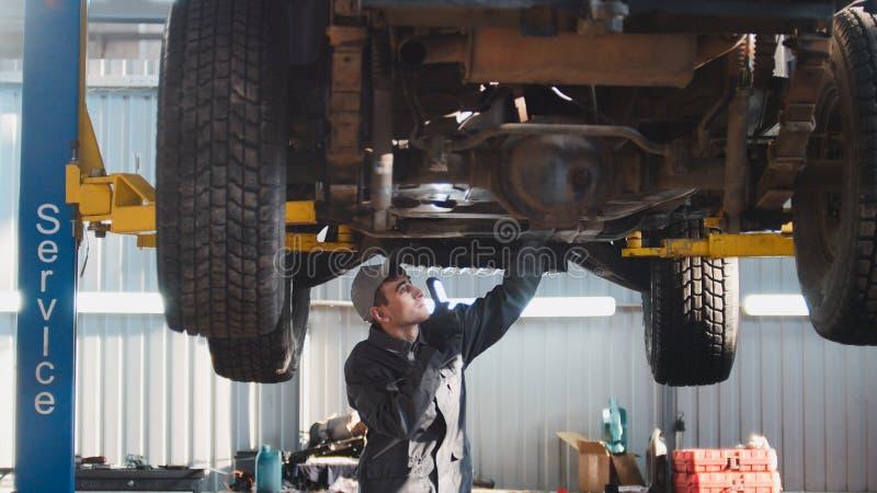 Bilservice - en mekaniker kontrollerar upphängningen av SUV, bred vinkel arkivbilder