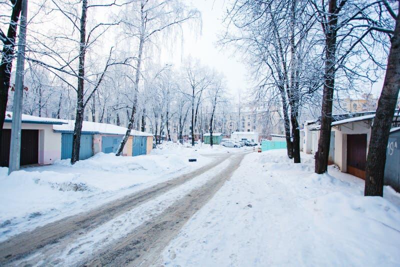 Bilspår som lämnas på den snöig hala vägen i vinter Träd i hoarf royaltyfri fotografi