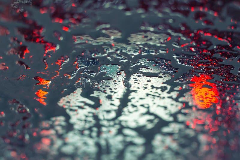 Bilspring till och med automatisk carwash Vindrutasikt från inre Abstrakt våt vindrutabakgrund Röda bromsljus av bilen royaltyfria bilder