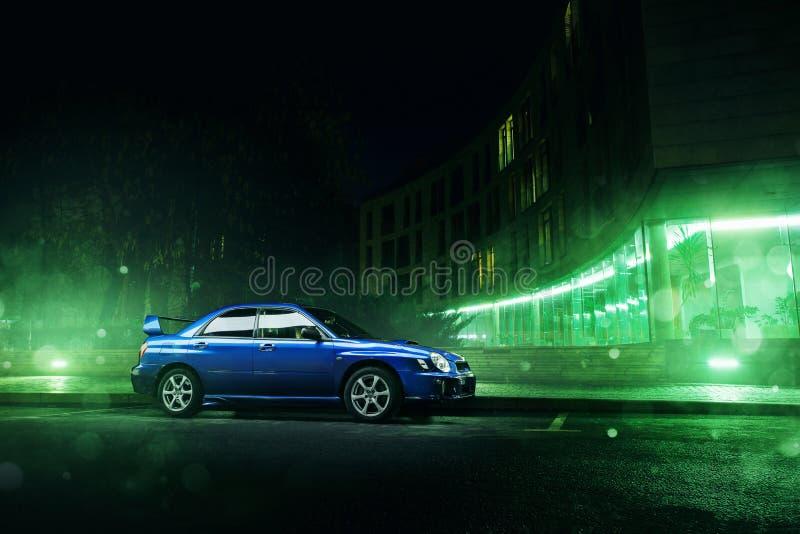 BilSubaru Impreza WRX ställning i Moskvastad nära moderna byggnader på natten arkivfoton