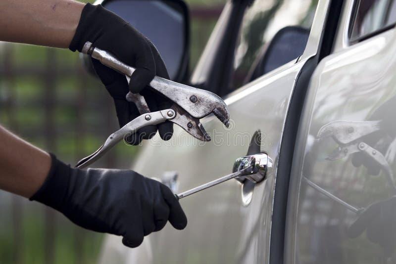 Biltjuv som använder ett hjälpmedel för att bryta in i en bil. arkivbilder