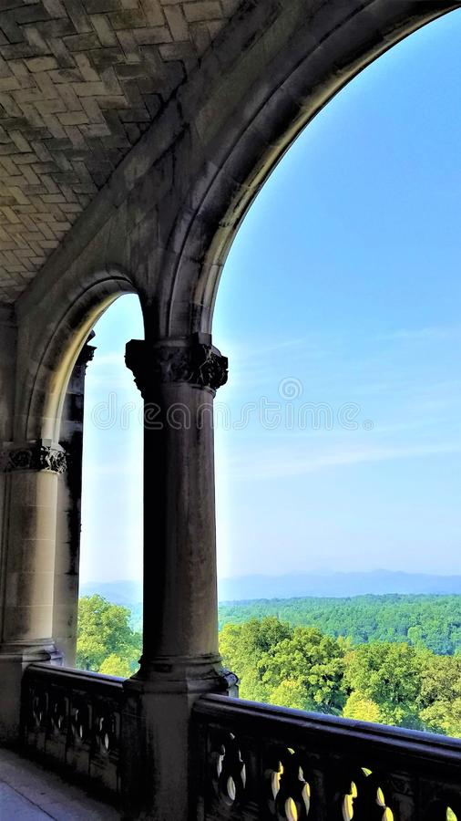 Biltmore veranda vista. Floor to ceiling arches on the veranda enable visitors to the Biltmore Hotel in Asheville, NC to enjoy a stunning elevated view of the royalty free stock photo