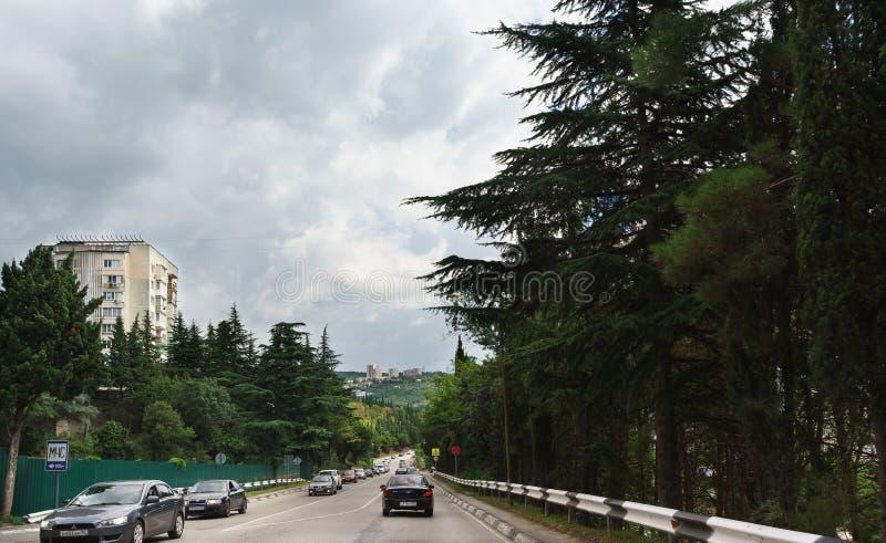 Biltrafik på den södra bankhuvudvägen på utkanten av semesterortstaden royaltyfri fotografi
