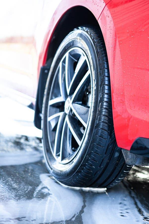 Biltvätt gör ren bilen, når den har tvättat sig med skum Hjuln?rbild arkivbild