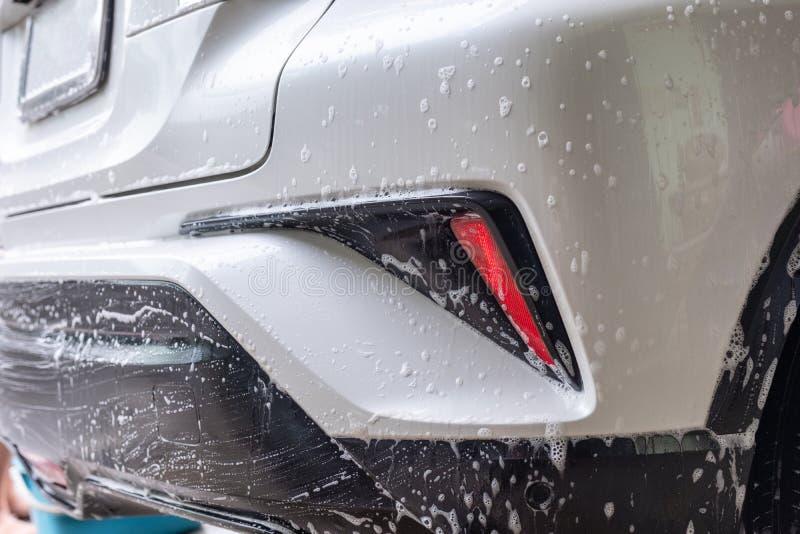 Biltvätt med bubblatvål på den bakre bilen arkivfoto