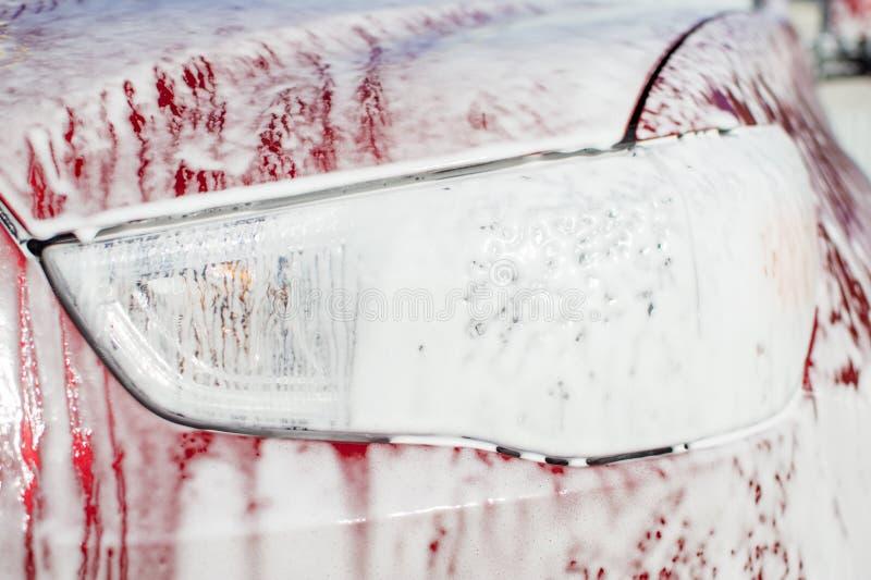 Biltvätt med ettkontakt skum, billykta med en tjock skumnärbild arkivbilder