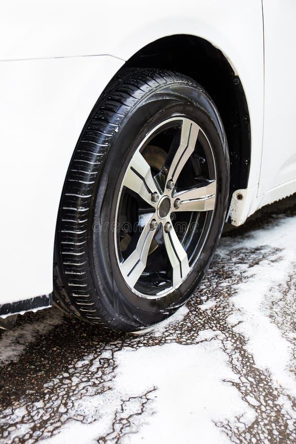 Biltvättbegrepp - bilhjul och skum arkivfoto
