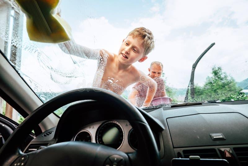 Biltvagningprocess: sonen hjälper hans fader att tvätta wi för en bilframdel royaltyfri bild