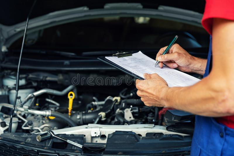 Bilunderhåll och reparation - papper för mekanikerhandstilkontrollista på skrivplattan arkivbilder