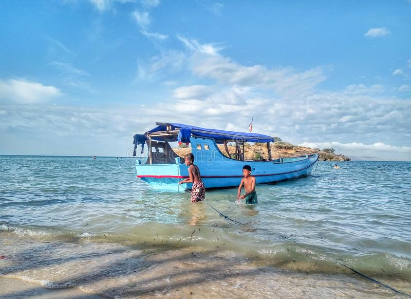 Bima, West Nusa Tenggara, Indonesia. July 3 2018 : Children play on the beach during summer vacation. Nature, boat, sea, tourist, guide, scenic, life, beauty stock photography