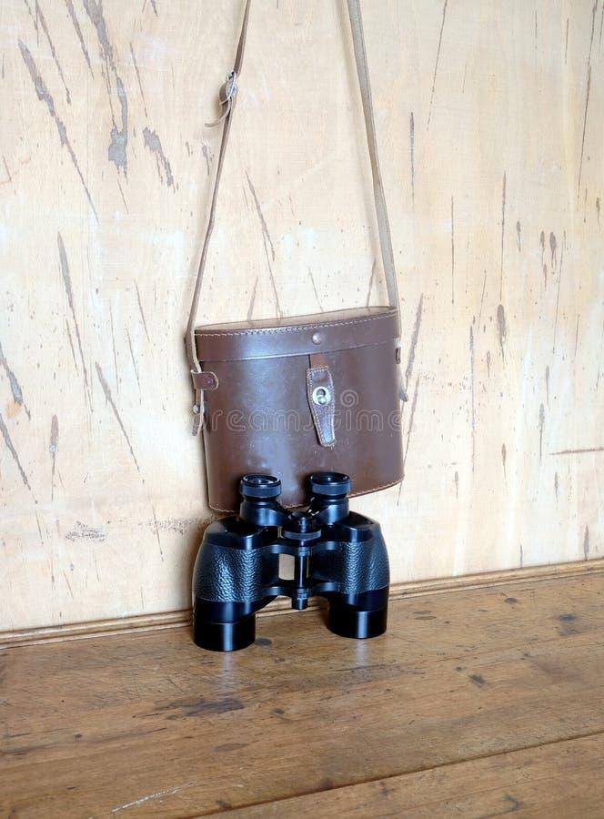 Binóculos da cor do preto de prisma do vintage e caixa de couro marrom na parede fotografia de stock