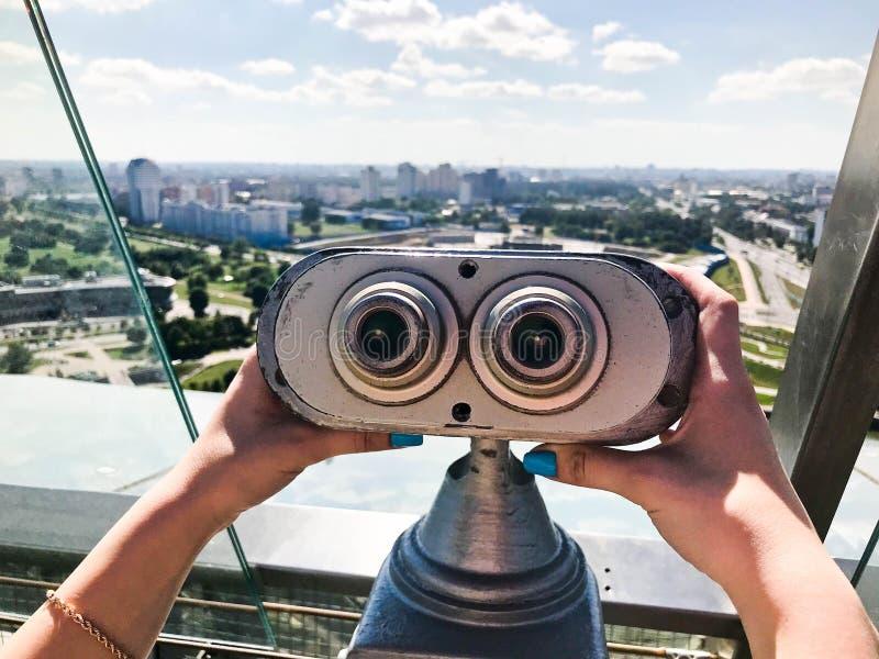 Binóculos estacionários de vista contra binóculos cinzentos na plataforma da visão na altura nas mãos de uma menina com prego col fotografia de stock