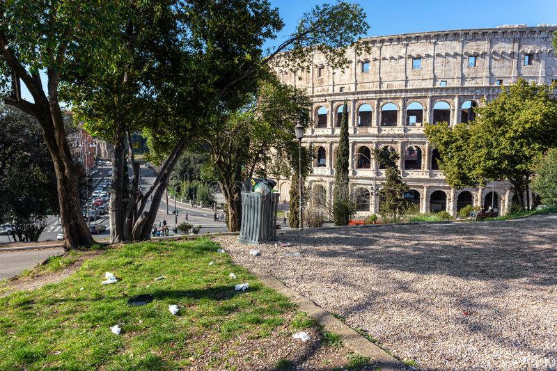 Bin and dirt, trash, on the background of the Italian monument to the Colosseum. Pollution in Rome. royalty free stock image