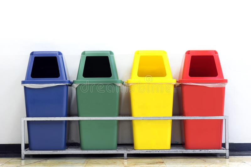 Bin, green, blue, yellow and red recycle bins with recycle waste symbol, Four colorful recycle bins garbage on wall white stock photography