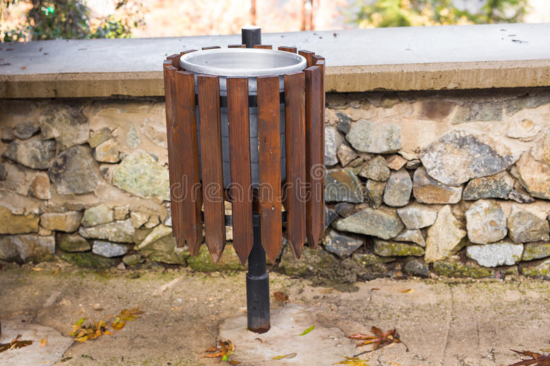 Bin in park. Trash can in a wooden frame royalty free stock photography