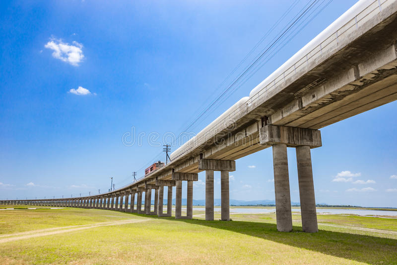 Binari ferroviari con il treno merci che passa il bacino idrico fotografia stock