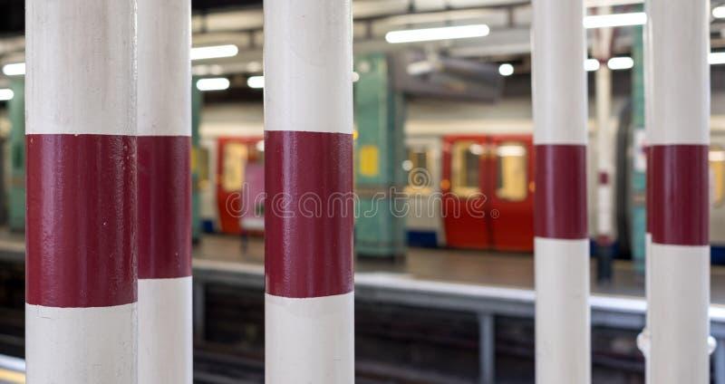 Binario alle colonne della stazione della metropolitana, di Londra di Aldgate ed al treno dipinti rappresentazione nel fuoco moll fotografie stock