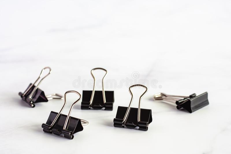 Binder clip on white marble background. With copy space for office and school supplies concept, selective focus and DOF stock photo