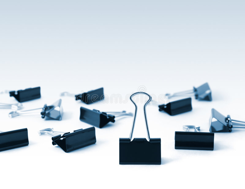 Binder Clips, Toned. A group of Binder Clips with one standing upright royalty free stock images