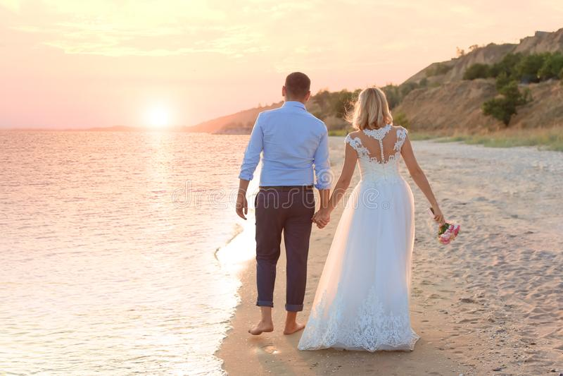 binder crystal smycken för parcravaten bröllop Brud och brudgum som går på solnedgången arkivfoto