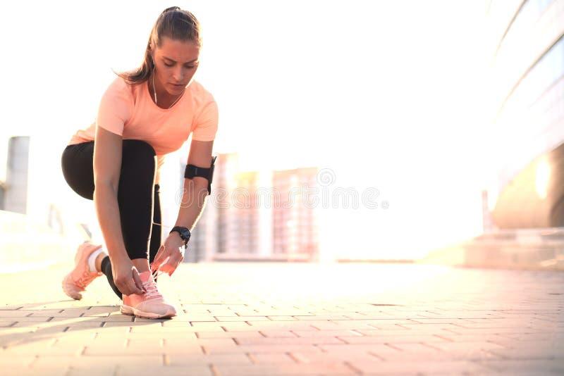 Binder den attraktiva sportiga flickalöparen för ung kondition upp skosnören på hennes sportskor som får klara att köra royaltyfria foton