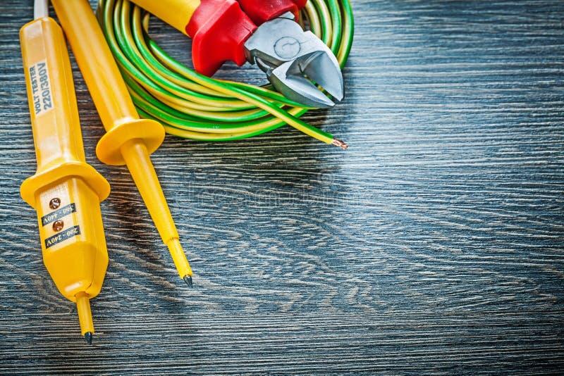 Binder den rullande bitande plattången för den elektriska testeren på det wood brädet arkivfoton