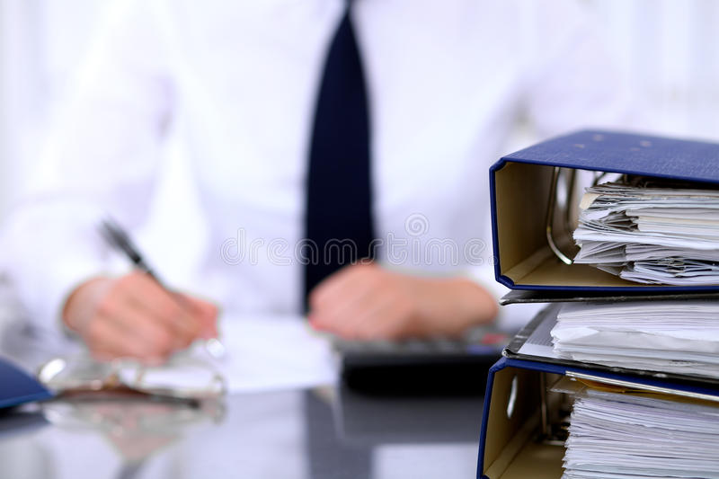 Binders with papers are waiting to be processed with business woman back in blur. Accounting planning budget, audit and. Insurance concept stock images