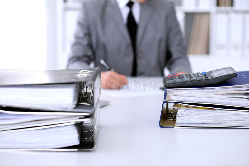 Binders with papers are waiting to be processed with business woman back in blur. Accounting planning budget, audit and. Insurance concept stock image