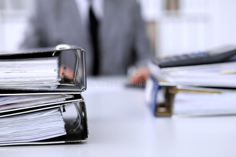 Binders with papers are waiting to be processed with business woman back in blur. Accounting planning budget, audit and. Insurance concept royalty free stock photography