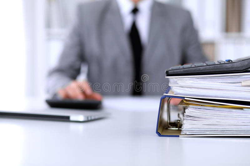 Binders with papers are waiting to be processed with business woman back in blur. Accounting planning budget, audit and. Insurance concept stock photo