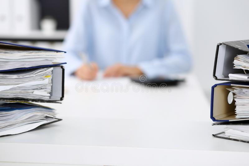 Binders with papers are waiting to be processed by business woman or bookkeeper back in blur. Internal Audit and tax. Calculator and binders with papers are royalty free stock image