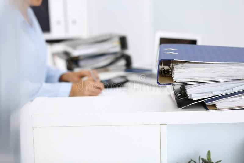 Binders with papers are waiting to be processed by business woman or bookkeeper back in blur. Internal Audit and tax. Calculator and binders with papers are stock images