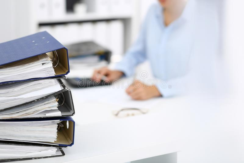 Binders with papers are waiting to be processed by business woman or bookkeeper back in blur. Internal Audit and tax. Calculator and binders with papers are stock image