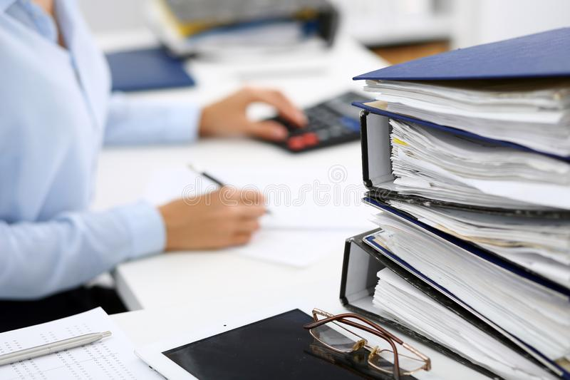 Binders with papers are waiting to be processed by business woman or bookkeeper back in blur. Internal Audit and tax. Calculator and binders with papers are stock photos