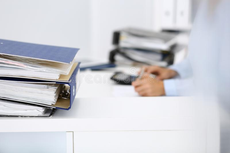 Binders with papers are waiting to be processed by business woman or bookkeeper back in blur. Internal Audit and tax. Calculator and binders with papers are royalty free stock images