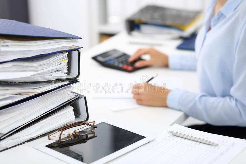 Binders with papers are waiting to be processed by business woman or bookkeeper back in blur. Internal Audit and tax. Calculator and binders with papers are royalty free stock photos