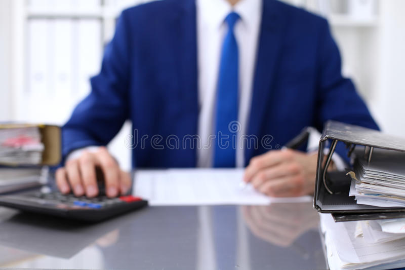 Binders with papers are waiting to be processed with businessman back in blur. Accounting planning budget, audit. Insurance and business concept royalty free stock photography